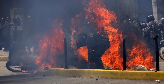 Las llamas rodean a varios policías tras el atentado de este domingo. - REUTERS