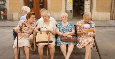 Cuatro mujeres mayores sentadas en un banco una plaza de Barcelona. AFP