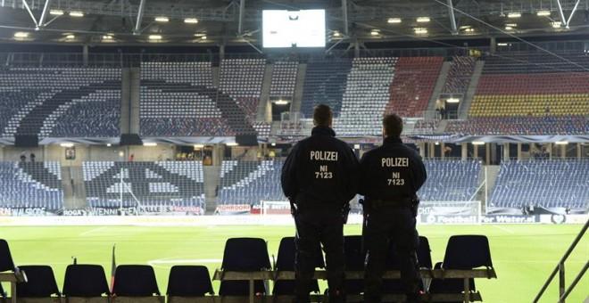 """17/11/2015. Dos agentes de la policía permanecen en las gradas antes del partido amistoso entre Alemania y Holanda en el IDH-Arena en Hannover (Alemania) hoy, 17 de noviembre de 2015. El IDH Arena ha sido evacuado por """"razones de seguridad"""" y el partido h"""