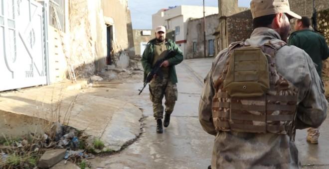 Milicianos asirios patrullan la aldea iráquí de Bakufa, a sólo unos cientos de metros de la posición del Estado Islámico. FERRÁN BARBER