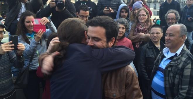 Alberto Garzón, líder de Izquierda Unida, y Pablo Iglesias, secretario general de Podemos, se abrazan en la Puerta del Sol de Madrid, para rubricar su acuerdo electoral. PODEMOS