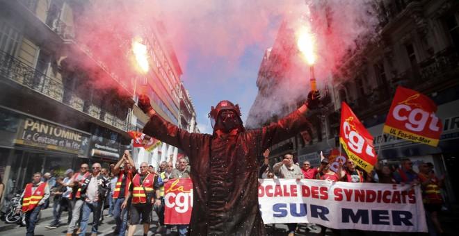 Un trabajador del acero, vestido con un traje de trabajo protector con una máscara de Darth Vader de Star Wars , portando bengalas durante una manifestación contra reformas laborales del Gobierno francés en Marsella, Francia.  REUTERS / Jean Paul Pelissie