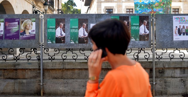 Una mujer habla por su móvil junto a varios carteles electorales en la localidad de Guernica. REUTERS/Vincent West