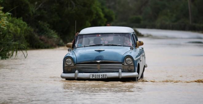Une voiture sur une route inondée de Guantanamo après l'ouragan Matthew. / ALEXANDRE MENEGHINI (REUTERS)