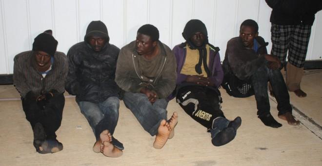 Varios migrantes se sientan tras ser detenidos por la guardia costera de Libia, en Trípoli, 5 de febrero de 2017. REUTERS / Hani Amara