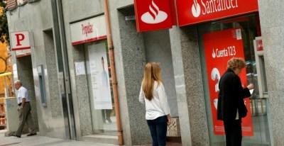 Un par de personas utilizan un cajero automático de una oficina del Banco Santander, en Barcelona, situada junto a una sucursal del Popular. REUTERS/Albert Gea