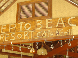 Photo of bent-wood sign above entrance to Puerto Beach Resort Cafe and Grill