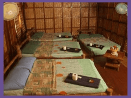 Photo of four beds made up in a room each with a slender tray holding identical sets of gifts