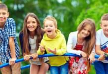 Fünf Kinder stehen auf einem Klettegerüst im Grünen und lächeln in die Kamera.