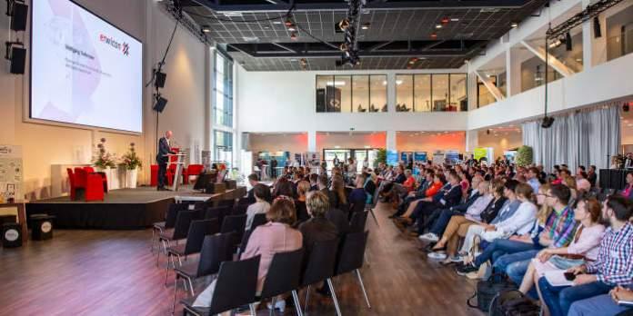 Zahlreiche Menschen sitzen in einem Saal in Kinobestuhlung und blicken zu einem Redner auf einem Podest.