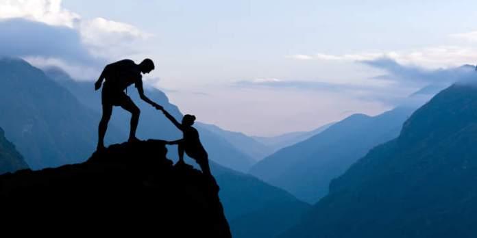 Die Silhouetten von zwei Personen erklimmen vor einer gewaltigen Bergkulisse in Blautönen einen Fels. Eine Person ist bereits oben und hilft der anderen beim Aufstieg.