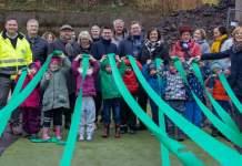 Kinder, Erwachsene und Offizielle mit grünen Bändern