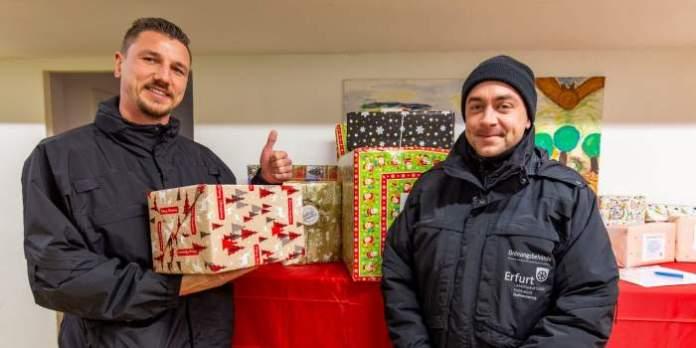 Zwei Männer in schwarzer Dienstkleidung stehen vor einem Tisch mit Geschenken.