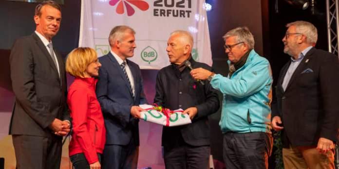 Fünf Herren und eine Frau auf einer Bühne der Buga 2019 in Heilbronn. Es wird eine Fahne übergeben.