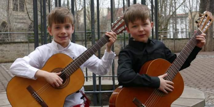 zwei Jungen spielen auf ihren Gitarren.