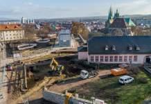 Luftbild auf Baustelle mit Häuserensemble und Mauern; im Hintergrund Altstadt von Erfurt