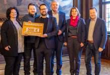 Vier Männer und zwei Frauen präsentieren einen Spendenscheck über 500 Euro