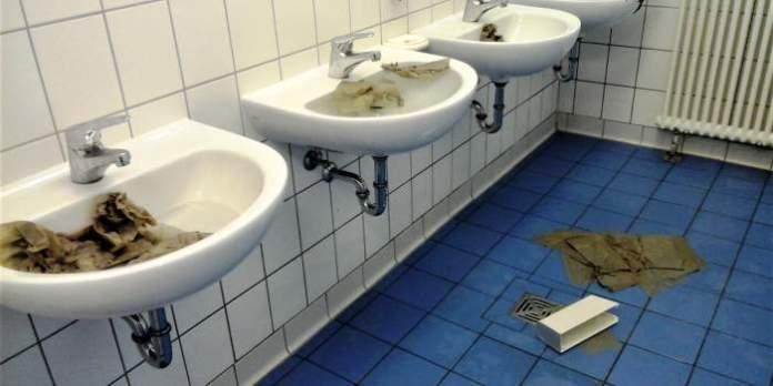 Mehrere Waschbecken, die mit Wasser befüllt und Papier verstopft wurden.