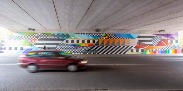 Eine bunt gestaltete Wand, vor der ein Auto fährt
