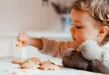 ein kleines Kind verziert gebackene Plätzchen