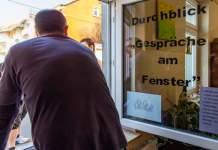 Ein Mann unerhält sich am Fenster mit Jugendlichen