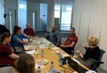 Eine Gruppe aus 7 Menschen sitzt mit Abstand zueinander an einem Tisch.