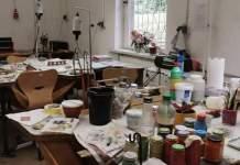 Goldschmiede-Werkstatt mit Tischen und Ablagen, vorne Gläser mit Email auf einem Tisch