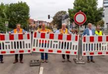 mehrere Männer heben eine Straßenabsperrung aus ihrer Verankerung