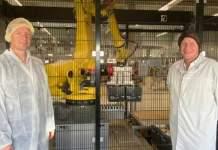 Zwei Männer in Hygienekitteln stehen vor einem eingezäunten Roboterarm in einer Produktionshalle.