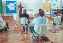 Ein Referent spricht zu seinem Publikum aus 7 Menschen, die in einem Abstand von über 1,5 m verteilt sitzen.