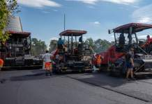 Drei große Straßenbaumaschinen und Bauarbeiter während der Arbeit