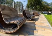 große Holzsessel stehen in einer Grünanlage