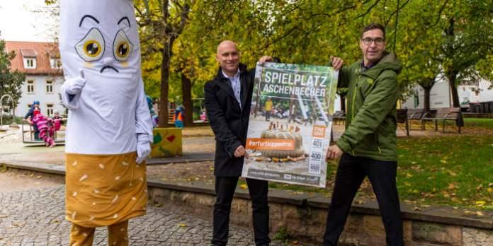 Zwei Männer halten ein Plakat. Neben ihnen steht eine übergrpße Figur in Form einer Zigarette.