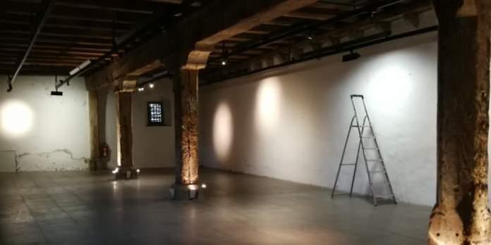 ein leerer Ausstellungsraum mit Säulen und Deckenbalken aus Holz