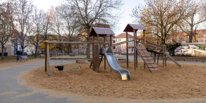eine Spielanlage mit Rutsche, Schaukeln und Klettermöglichkeiten auf einem Spielplatz