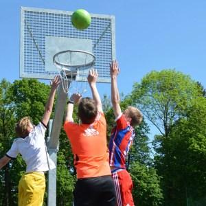 Drei Jungen von hinten aufgenommen beim Korbwurf auf dem Basketballfeld