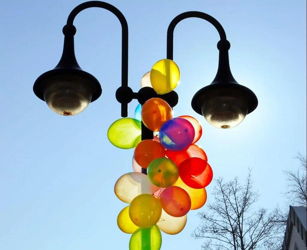 Mit bunten Luftballons geschmückter Laternenpfosten zur Faschingsfeier am Kirchplatz