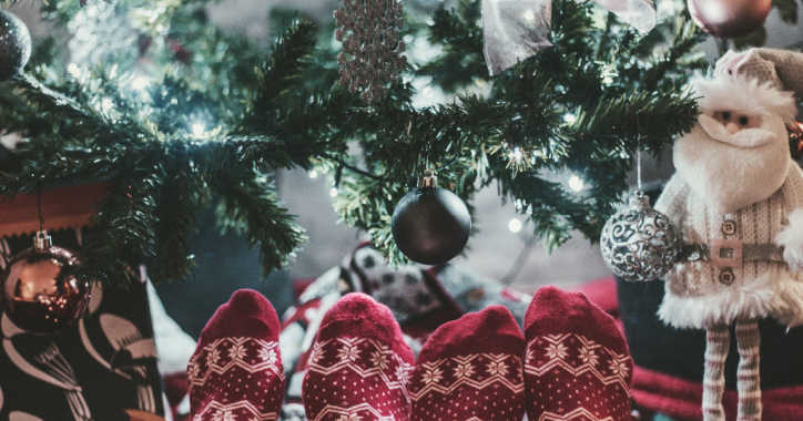 Feet in Christmas socks in front of a Christmas tree