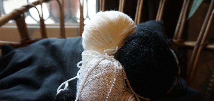 laine noire et blanche posée sur un coussin noire et une chaise en osier