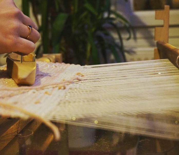 tissage fait sur un métier de table avec des couleurs rose et or