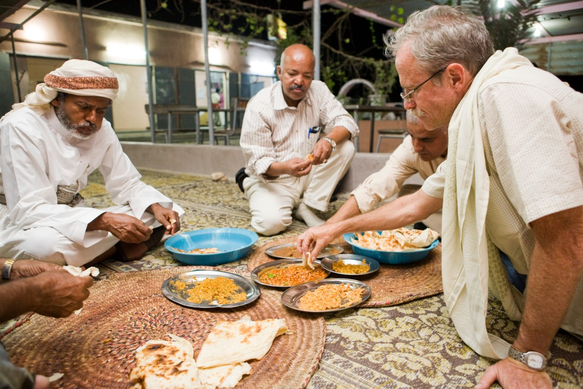 Arabian Leopard (Panthera pardus nimr) researcher David Stanton eating local food with Yousuf Mohageb, Mohammed Shamsan, and the minister of environment, Yemen