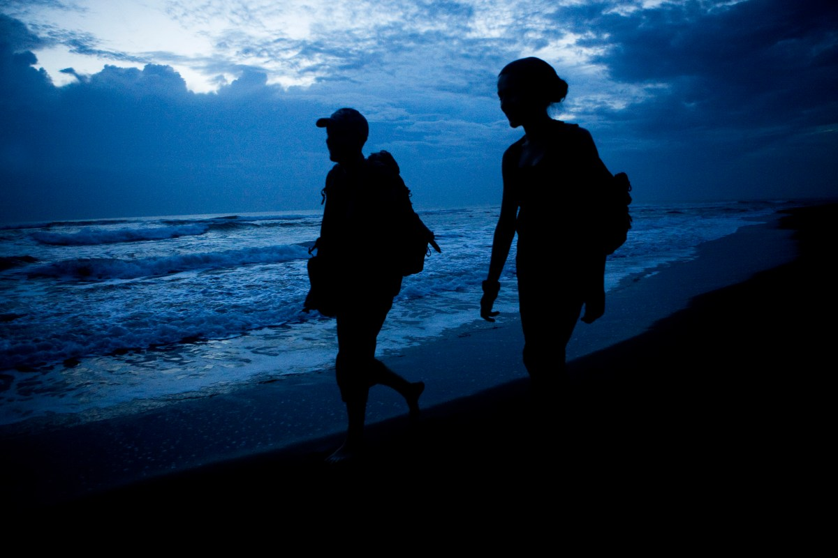 Jaguar (Panthera onca) biologists, Stephanny Arroyo-Arce and Ian Thomson, walking down beach to check for predated sea turtles at dawn, Coastal Jaguar Conservation Project, Tortuguero National Park, Costa Rica