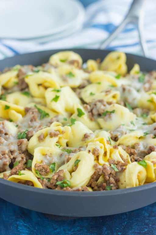 This Cheesy Beef Tortellini Skillet is a simple, one pan meal that's bursting with flavor. Loaded with ground beef, spices, tortellini, and cheese, this easy meal is family-friendly and so delicious!