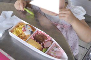 ハローキティ新幹線弁当を食べる子供