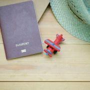 Titolo viaggiare e conoscere immagine di passaporto, modellino aereo e cappello su un tavolo