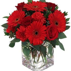 composizione con rose rosse e gerbere rosse in vaso di vetro