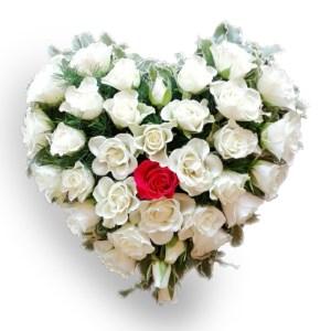 composizione a forma di cuore con rose bianche e una rosa rossa al centro