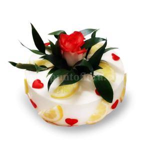Torta guarnita con spicchi di limone cuoricini rossi e bocciolo di rosa al centro