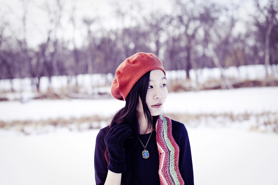 Self-portrait photography in the snow. Outfit details: Parkhurst red beret, Forever21 black wavy dress, Fox zigzag striped wool scarf, Urban Outfitters landscape printed tights, Fila black men's boots, Simply Willow brilliant green opal necklace from Etsy.