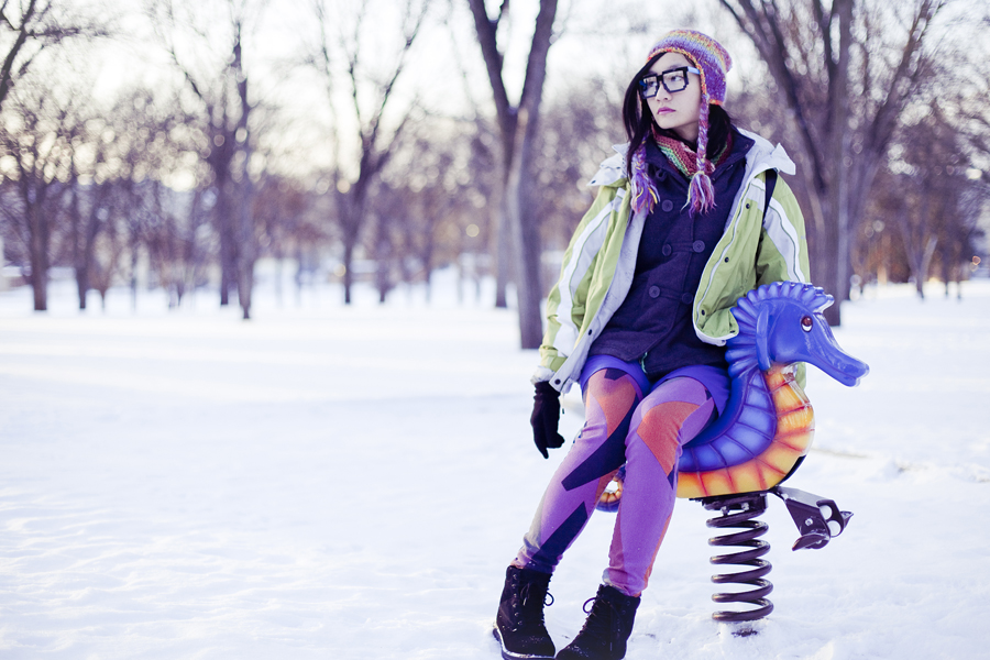 Photoshoot in the snow, on a rocking sea horse. Outfit details:  Passport Love blue ruched dress, Urban Outfitters BDG patchwork jeans, Fox striped zigzag scarf, Forever21 colourful beanie, Dollhouse grey jacket, Fila black men's boots, geeky 8-bit glasses, T-shirt & Jeans patterned backpack.
